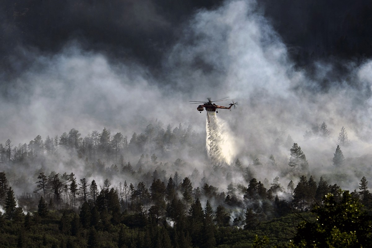 Helicopter dropping water on a forest fire
