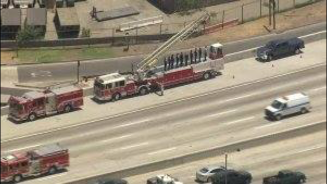 Firefighters salute the van carrying the body of slain Long Beach Fire Capt. Dave Rosa as it travels down the 710 Freeway en route to the coroner's office on June 25, 2018. (Credit: KTLA)