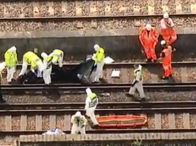 Rescue workers on the train tracks.