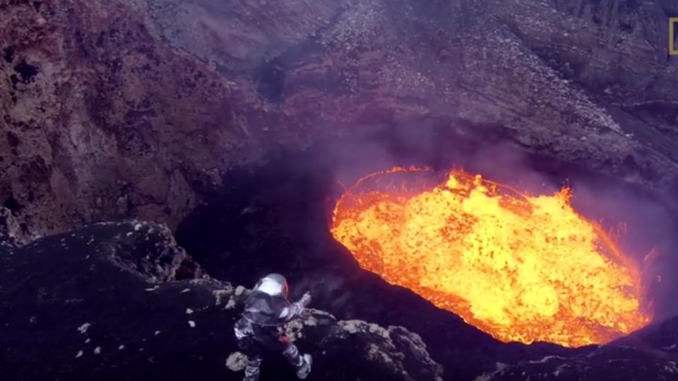 Man in heat protective suit at the edge of a volcano. Photo: National Geographic