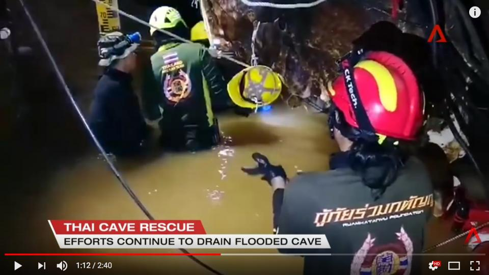 The rescue personelle working in the muddy waters of the cave in Thailand.
