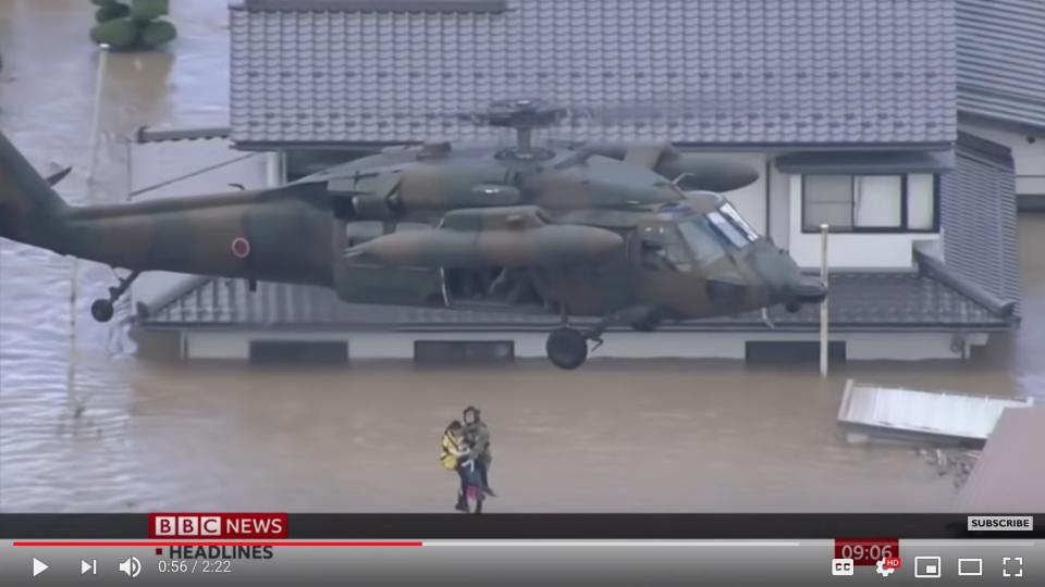 A helicopter rescue team rescues a civilian from a flooded home. Screen shot from a BBC Youtube video.