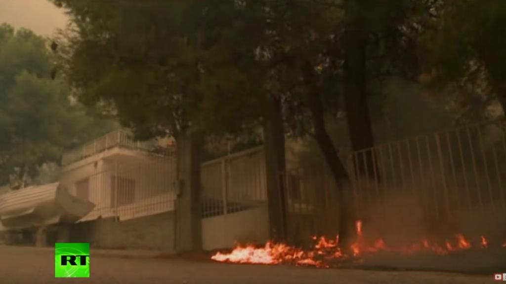Forest fire near a home in Greece.