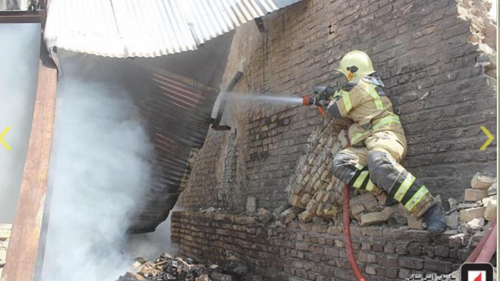 Firefighter in Iran fighting a warehouse fire