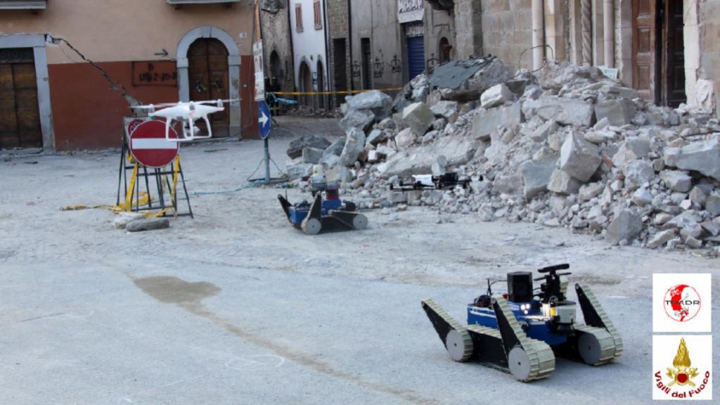 Two UGVs and two UAVs in front of the San Francesco church. Photo Credit: TRADR